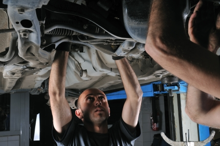 Auto mechanics working under the car photo