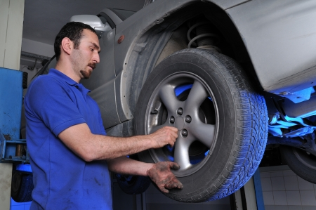 Car mechanic removing wheel nuts to check brakes - a series of MECHANIC related images  photo