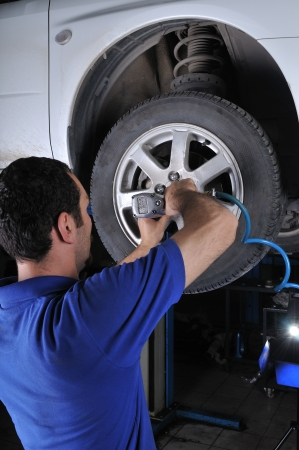 auto shop: Car mechanic removing wheel nuts to check brakes - a series of MECHANIC related images