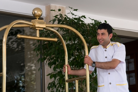 accommodation: Bellboy with luggage cart Stock Photo