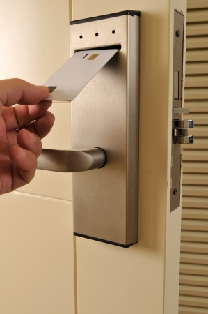 A hand inserting keycard in the electronic lock - a series of HOTEL images