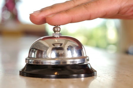 Hand of a man using a hotel bell - a series of HOTEL images photo