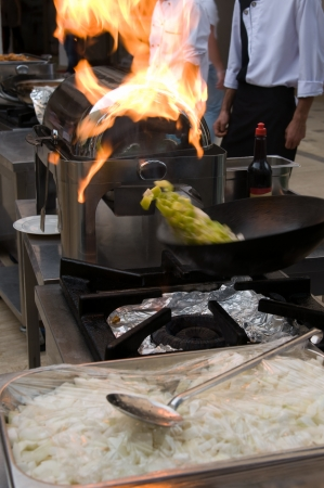 Professional cook preparing food on flame  photo