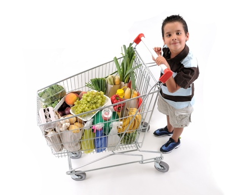 Cute boy with shopping trolley isolated on white.