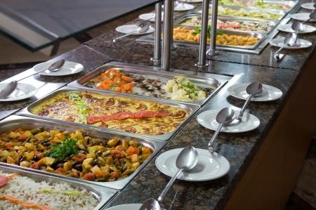 buffet food: Met�licos bandejas de comida para banquetes que se presentan en las tablas