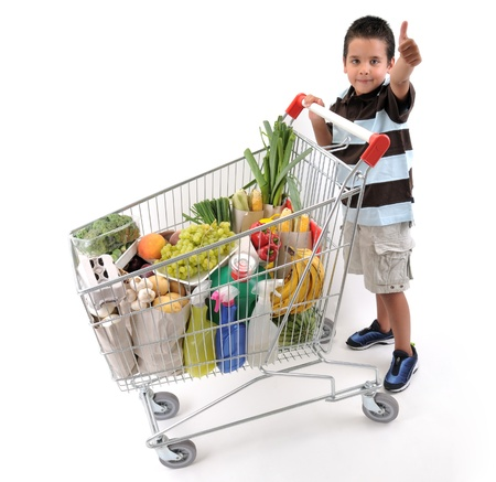 supermarket cart: Cute boy with shopping trolley isolated on white