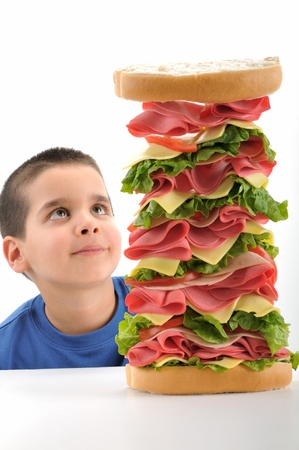 out to lunch: Cute boy looking at a big sandwich isolated over white background