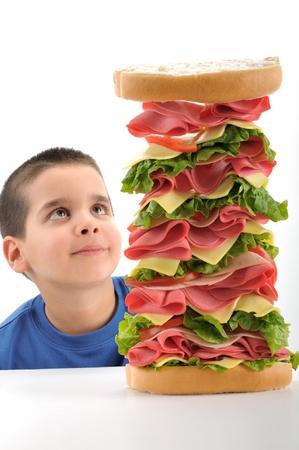 sandwich: Ni�o lindo mirando un s�ndwich grande aislado sobre fondo blanco Foto de archivo
