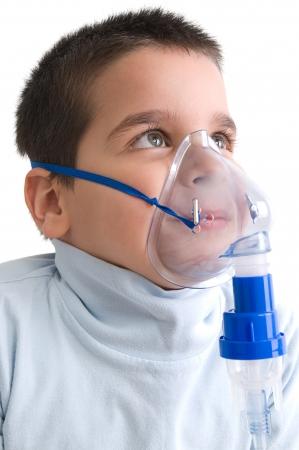 酸素マスクを用いた喘息の小さな男の子のイメージを閉じます