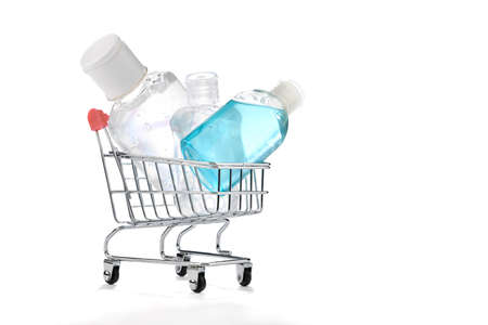 Shopping cart full of hand sanitizers isolated on white background.   Lots of  alcohol gel in shopping cart. Imagens