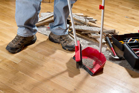 An unrecognizable person with a broom sweeping floor into dustpan