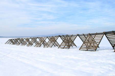 tillage: He is a snow-fence on a snowy tillage.