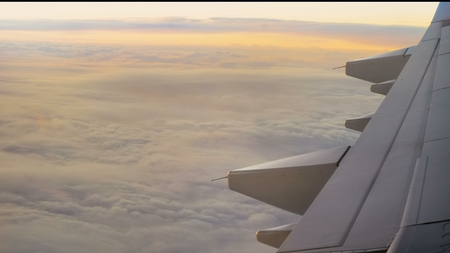 Airliner over the clouds in the rays of a beautiful sunset