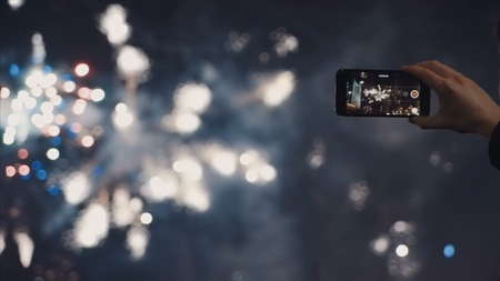 A man shoots a selfie video of a festive pyrotechnic show in a night city 写真素材