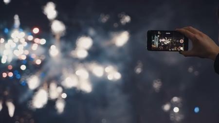 A man shoots a selfie video of a festive pyrotechnic show in a night city Reklamní fotografie