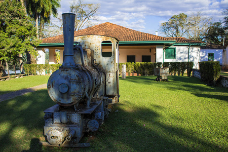 Old locomotive machine in the garden of a ruined mansion Stock Photo