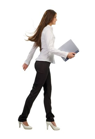 businesswoman with laptop a young businesswoman walking and holding a laptop, isolated on white background photo
