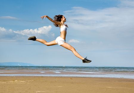 flying girl Young woman making exercise on the beach. photo