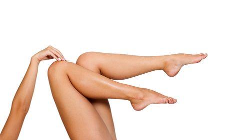 Two woman legs with moisturizer body cream photo