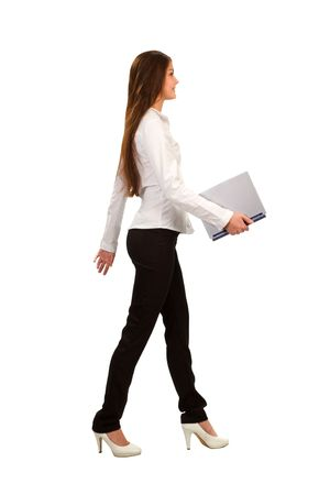 a young businesswoman walking and holding a laptop,  isolated on white background photo