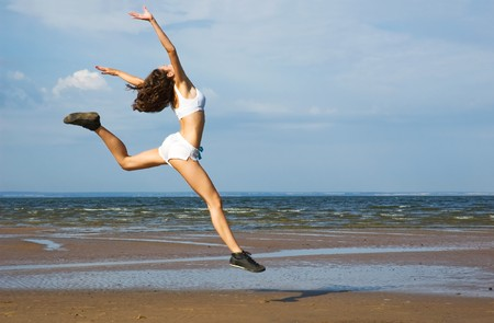 Young woman making exercise on the beach.