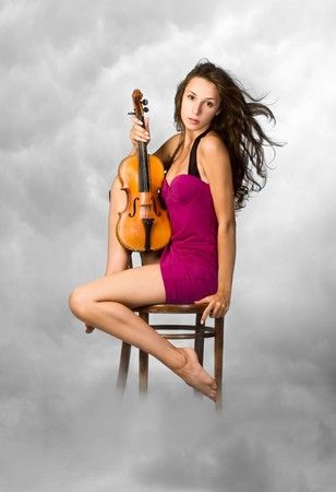 pretty young woman  in purpl dress holding old viola in her hands photo