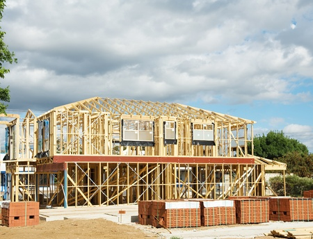 subdivisions: New residential construction home framing against a blue sky.