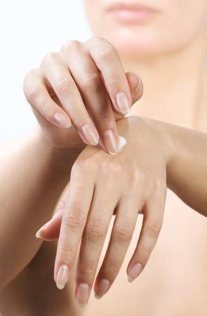 woman hands applying moisturizing cream to her skin photo