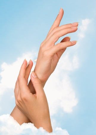 Two woman hands with moisturizer body cream against the sky Stock Photo - 8485577