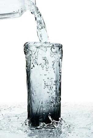 vaso de un agua con desbordamiento sobre fondo blanco Foto de archivo