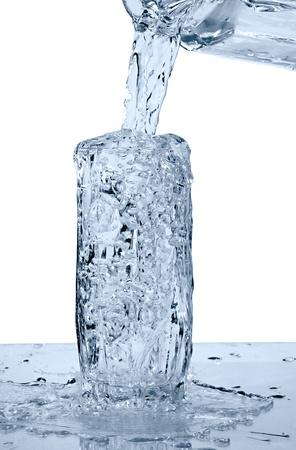 vaso de un agua con desbordamiento sobre fondo blanco