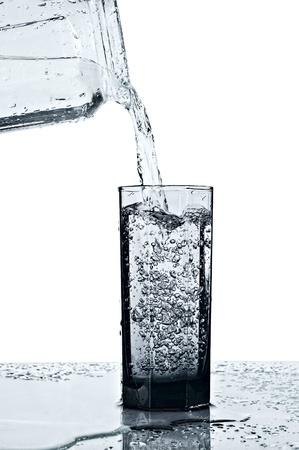 overflow: fresh water being poured into a glass with overflow isolated on white