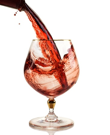 red wine being poured into a wine glass photo