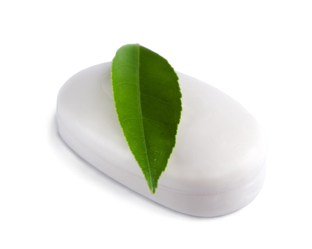 White soap bar with green leaf isolated on white background. photo