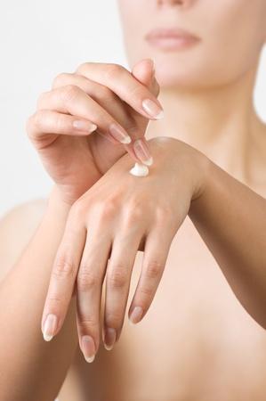 Woman hands applying moisturizing cream to her skin.Shallow focus photo