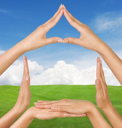 Female hands showing conceptual home symbol over summer landscape  background photo