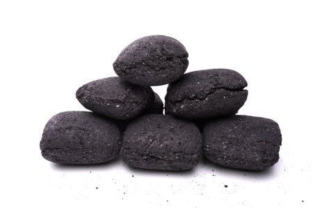 heap of coal briquette for BBQ isolated on white photo