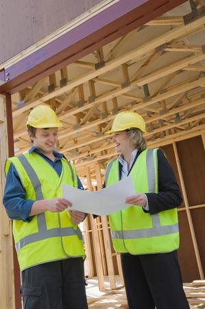 ingeniero civil: ingeniero civil y trabajador debatir cuestiones en el sitio de construcci�n Foto de archivo