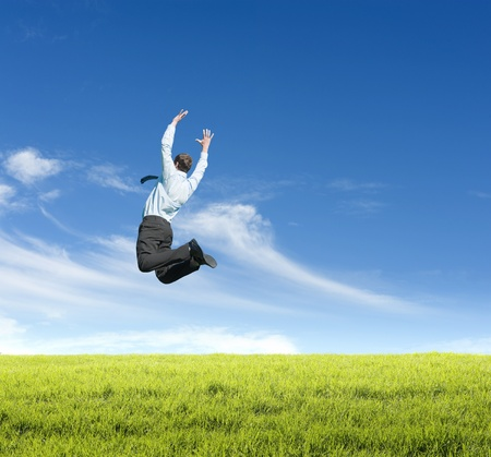 happy young man jumping on meadow against clear sky background Stock Photo
