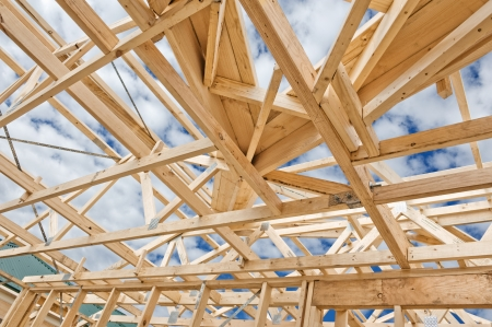 material: Fragment of a new residential construction home framing against a blue sky