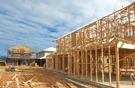 Fragment of a new residential construction home framing against a blue sky. photo