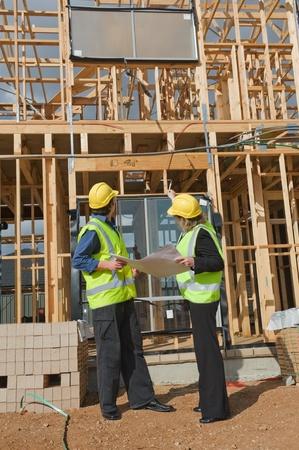 supervisores: ingeniero civil y trabajador debatir cuestiones en el sitio de construcci�n Foto de archivo