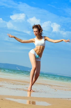 Young beautiful woman dancing on the beach  photo