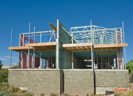 roof framing: new home currently under construction against blue sky Editorial