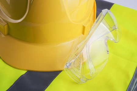 eye protectors: Yellow vest and helmet with protection glasses close up