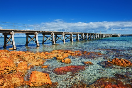 australia landscape: Sea landscape with wooden pier and orange stones