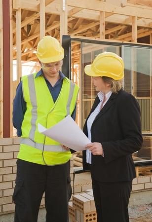 ingeniero civil: ingeniero civil y los trabajadores discutir temas en el sitio de construcci�n