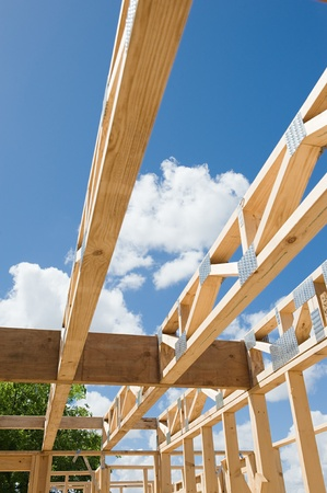 roof framing: New residential construction home framing against a blue sky.