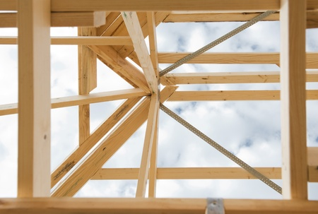 New residential construction home wooden framing against a cloudy sky photo