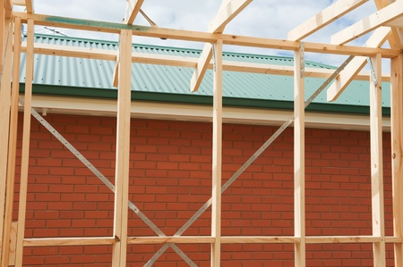 Fragment of a new residential construction home framing against a blue sky. Stock Photo - 11120874